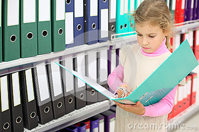 Serious looks at folder and stands near to shelves