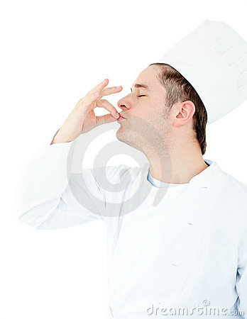 Serious male cook showing the sign for delicious