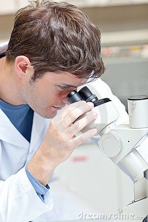 Serious male scientist looking through microscope