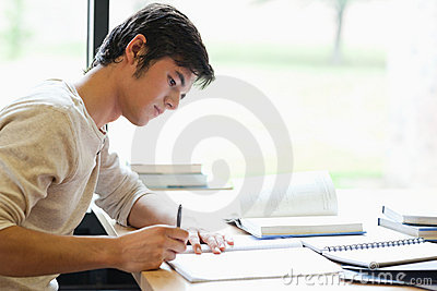 Serious male student writing