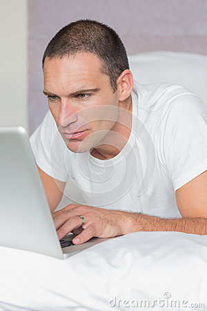 Serious man lying on bed using his laptop