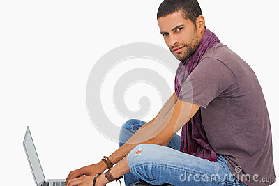 Serious man wearing scarf sitting on floor using laptop