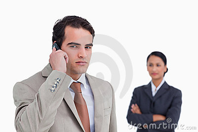 Serious salesman on his cellphone with colleague