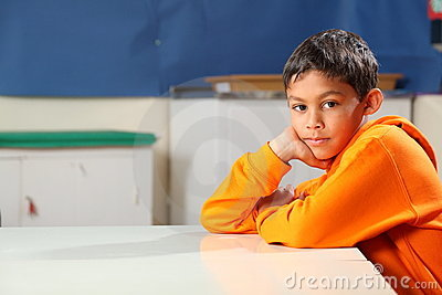 Serious school boy 10 deep thought in classroom