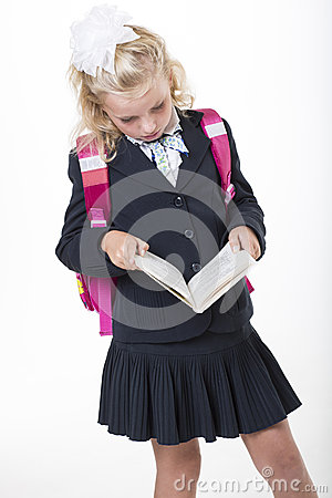 Serious school girl reads a book