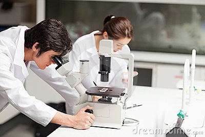 Serious science students using a microscope