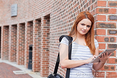 Serious student holding a tablet computer