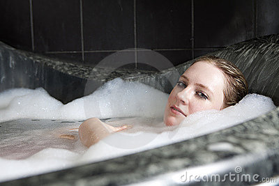 Serious woman enjoys the bath-foam in the bathtub.