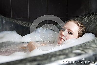 Serious woman enjoys the bath-foam in the bathtub.