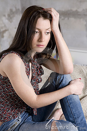 serious woman in jeans having hole sitting on s