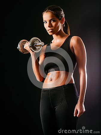Serious woman lifting a dumbbell