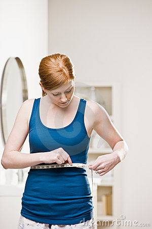 Serious woman measuring her waist