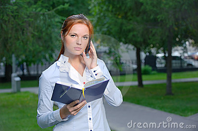 Serious woman with notebook talking on the phone