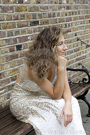 Serious woman sitting on bench  at bus stop