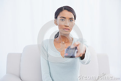 Serious woman sitting on sofa changing tv channel