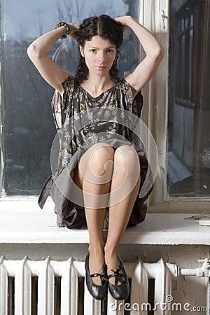 serious woman sitting on windowsill.