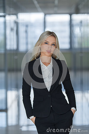 Free Serious Young Businesswoman With Hands In Pockets Looking At Camera Royalty Free Stock Photography - 80539077