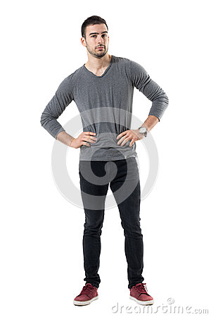 Free Serious Young Casual Man With Hands On Waist Looking At Camera Stock Photos - 91647593