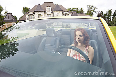 Serious young woman driving away from house
