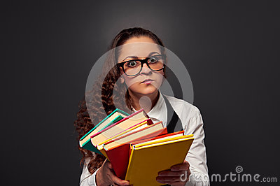 Serious young woman in glasses offering books
