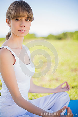Serious young woman meditating in lotus position