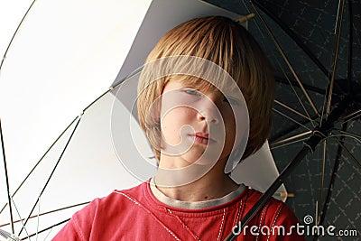 Seriouse boy with umbrellas
