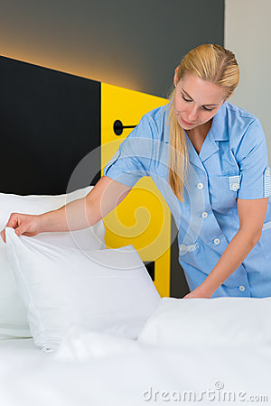 Service in hotel, maid puts clean sheets on bed