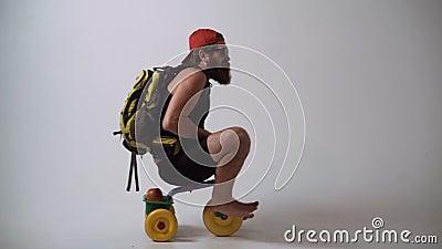 Servicio de salida No entrega de bebé Un hombre barbudo divertido está montando una bicicleta del ` s de los niños almacen de metraje de vídeo