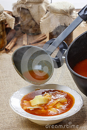 Serving tomato soup. Pouring soup in a plate