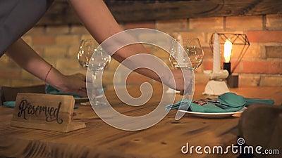 Servitris som sätter vinexponeringsglas på tabellen för romantisk matställe med stearinljus i lyxig restaurang Tjänande som tabel arkivfilmer