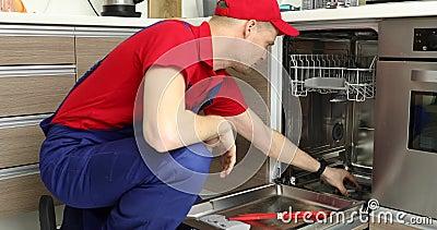 Servizio di manutenzione dell'elettrodomestico - riparatore che lavora con la lavastoviglie stock footage