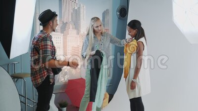 Sesja fotograficzna w nowoczesnym studio: Stylista i fotograf wybierają ubrania na sesję zdjęć czarnego modelu zbiory