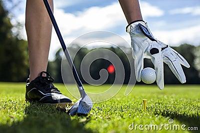 Set golf ball on a peg on field