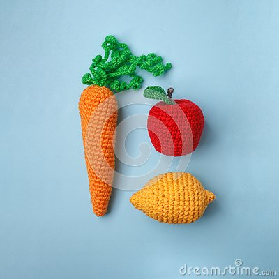 Free Set Of Knitted Toys Lemon, Carrot, Apple On Blue Background. Earlier Tactile Development Of Children, Craft Toys, Vegetarian Menu Royalty Free Stock Images - 127771519