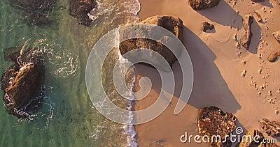 Setzen Sie Luftspitzenschuß auf dem Sonnenuntergang mit den Wellen auf den Strand, die Sandfelsen zerschmettern stock video footage