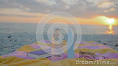 Setzen Sie Zubehör, eine Flasche Wasser, Tuch, Sonnenbrille, Lichtschutz und ein Buch auf den Strand stock video footage
