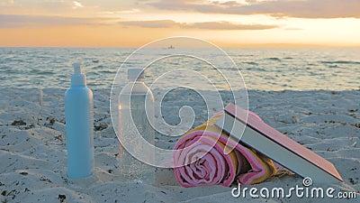 Setzen Sie Zubehör, eine Flasche Wasser, Tuch, Sonnenbrille, Lichtschutz und ein Buch auf den Strand stock footage
