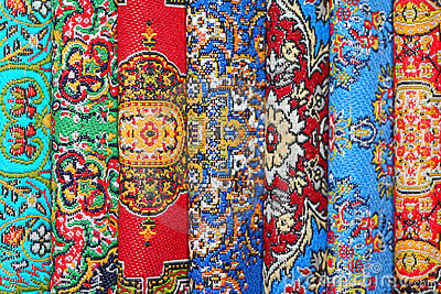 Seven carpets lie in rouleau on each other