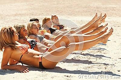 Several girls in bikini lying on sandy beach