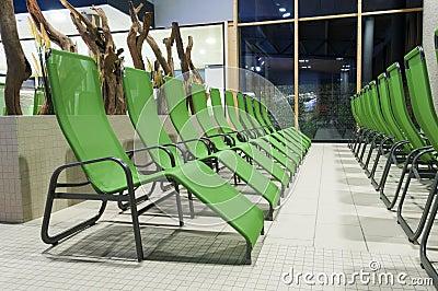 Several green swimming bath sun lounger