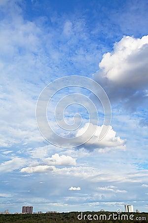Several white cumulus clouds under city