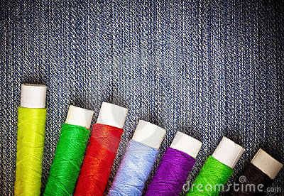 Sewing thread reels on blue denim