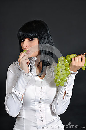 The sexual brunette with grapes