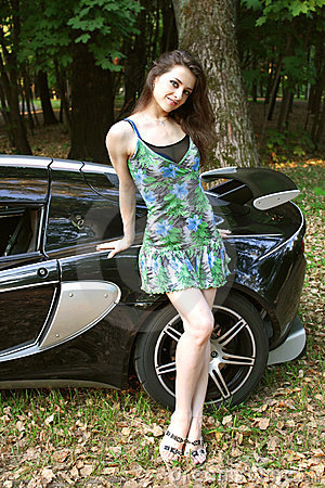 The sexual girl in standing near the sport car