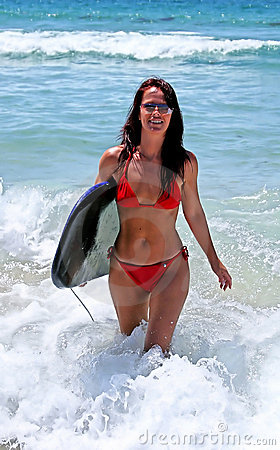 Sexy attractive young woman in red bikini walking in from blue sea on sunny beach with body board.