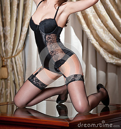 beautiful body shot of young woman wearing black lingerie and stockings. Long legs in black stockings on table. Perfect body Stock Photo
