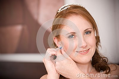 Sexy beautiful bride inserting her earrings