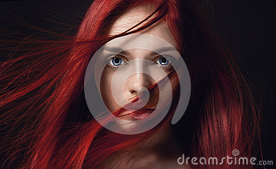 beautiful redhead girl with long hair. Perfect woman portrait on black background. Gorgeous hair and deep big blue eyes Stock Photo