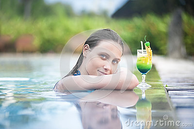 Sexy woman relaxing in the pool with a cocktail