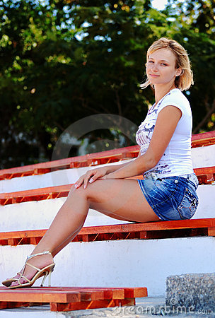 Sexy blond girl posing in a short jeans skirt